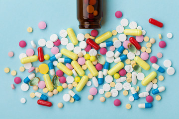 Colorful drug pills on blue background, pharmaceutical concept