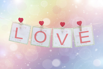 love symbol and hearts hanging on the clothesline with blank note for text