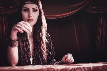 Composite image of portrait of fortune teller with pendulum