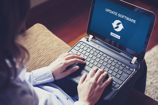 Update Software message in a laptop screen. Woman updating laptop software at home.