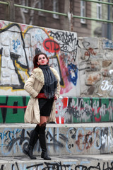 Beautiful woman in winter fashion standing on stairs with graffiti