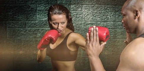 Composite image of female boxer practicing with trainer