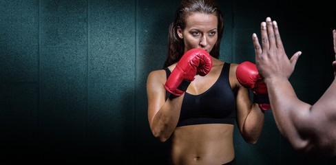 Female boxer with fighting stance against trainer
