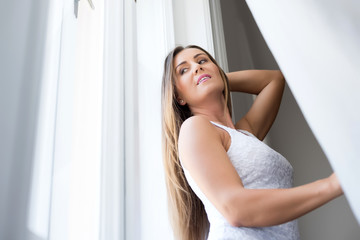 Beautiful young woman standing at the window
