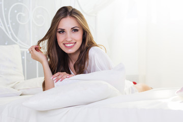 Pretty smiling girl is lying in bed with pillows