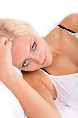Blonde girl lying sideways in bed
