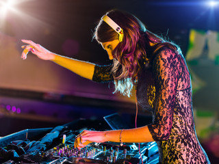 Beautiful DJ girl mixing electronic music