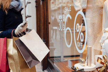 Woman with shopping bags in front on shop window
