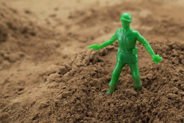 toy green soldier on sand