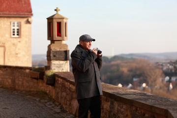 Elderly tourist taking a picture of a historic town