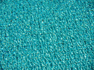 light reflection on water surface of swimming pool with turquoise color tiles on the bottom