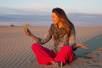 Young woman sitting on the sand in the desert and talking on Skype