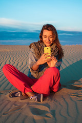 Young woman sitting on the sand in the desert and is looking at the phone