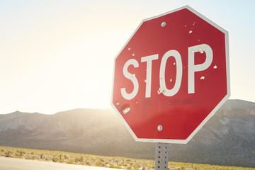 Stop Traffic Sign With Bullet Holes On Country Road