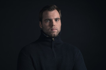 Winter fashion man wearing dark blue turtleneck.