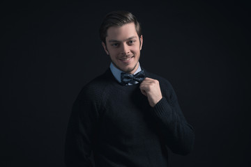 Smiling man wearing dark blue sweater and light blue shirt holdi