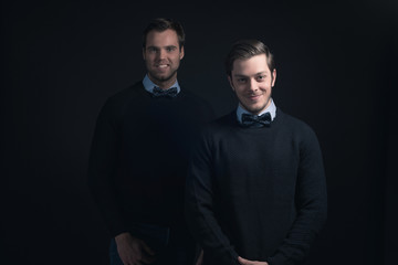 Two smiling men in dark blue sweater with shirt and bow tie.