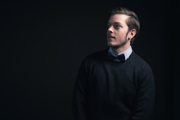 Man wearing dark blue sweater and light blue shirt with bow tie.