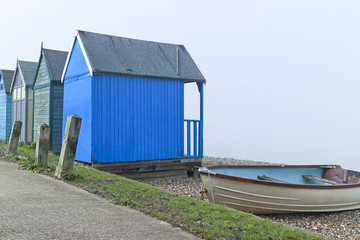 Blue wooden beach huts and old fishing boat by a footpath on British seaside on a foggy day