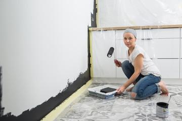 Woman paint wall at home.