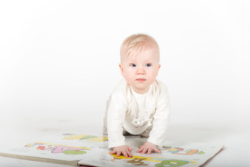 Little baby with the book on the white
