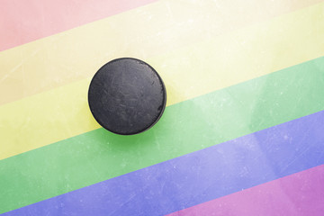 old hockey puck is on the ice with gay flag