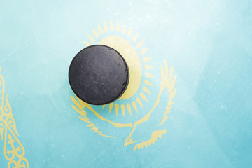 old hockey puck is on the ice with kazakhstan flag