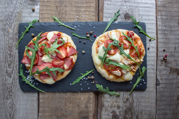 two mini pizzas and fresh arugula