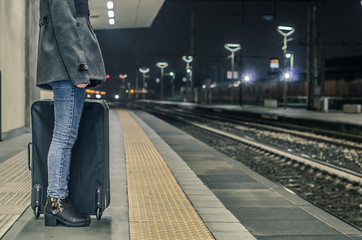 Girl is waiting the train with her suitcase at the station - people, travel and lifestyle concept