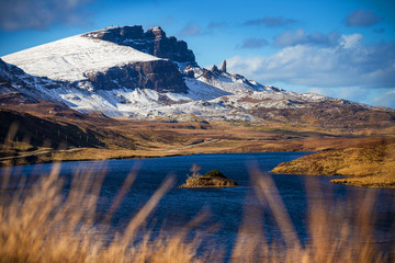 Wall Mural - Lock Fada and the snowy Old Man of Storr at spring time with blue sky - Isle of Skye, Scotland, UK