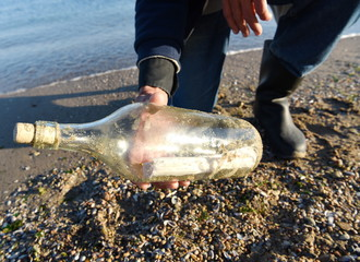 sunny beach / fisherman found a bottle with message