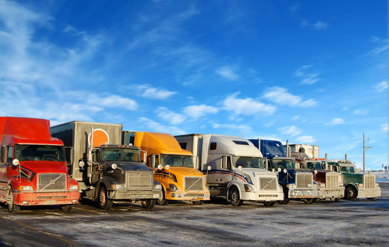 Multiple trucks park in a large parking lot
