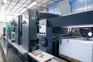 Operatore controlla stampante industriale a 5 colori