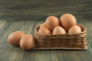 Huevos en canasta sobre mesa de madera.