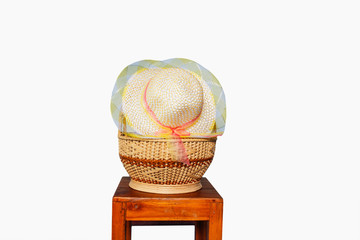 Hats woven in the basket on a white background on the chair.