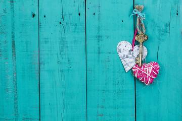 Skeleton key and hearts hanging on rustic door