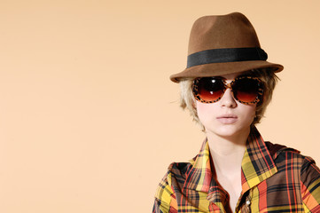 Portrait of young woman in cap with sunglasses