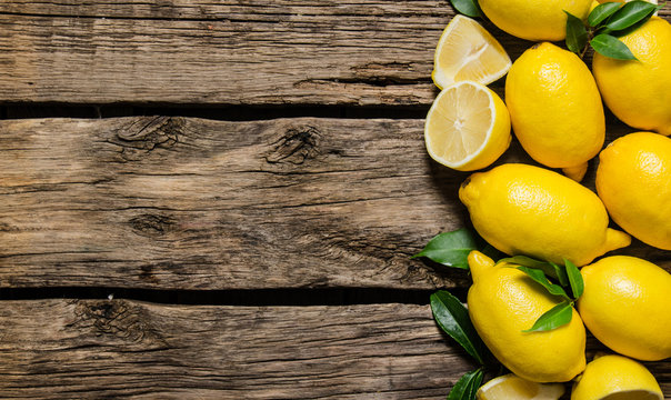 Fresh lemons with leaves. On wooden background.