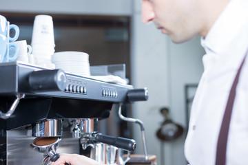 Bartender puts the holder in coffee machine