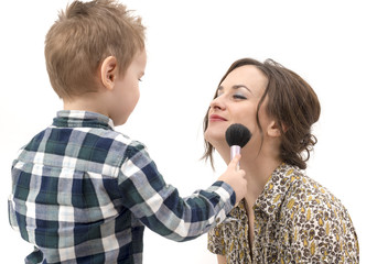 little boy putting on the makeup to her mother