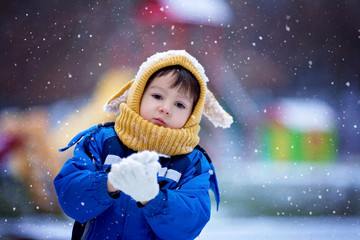 Cute little boy, playing with snow in the park, playground