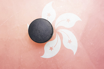 old hockey puck is on the ice with hong kong flag