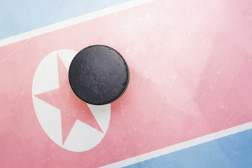 old hockey puck is on the ice with north korea flag