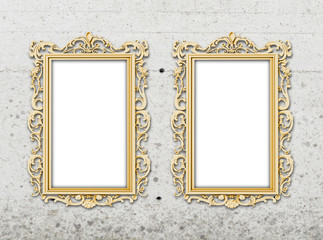 Close-up of two golden baroque picture frames on concrete wall background
