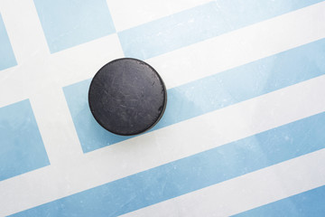 old hockey puck is on the ice with greece flag