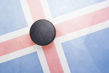 old hockey puck is on the ice with iceland flag