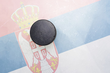 old hockey puck is on the ice with serbia flag
