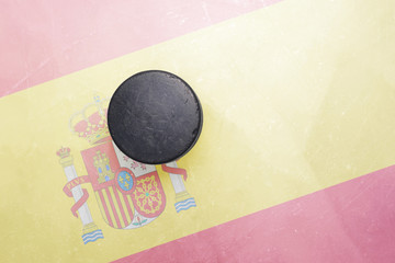 old hockey puck is on the ice with spain flag