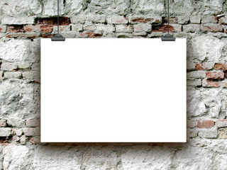 Close-up of one hanged paper sheet with clips on damaged brick wall background