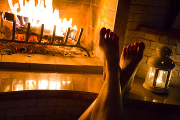 Female legs basking at home fireplace